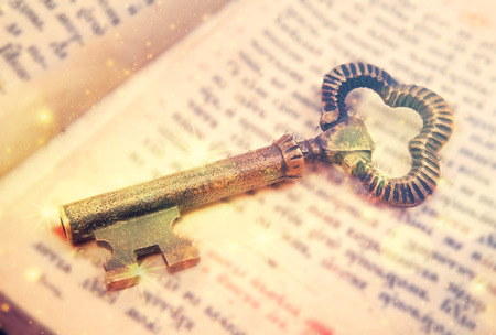 Antique key on old book. Glitter colorful background.
