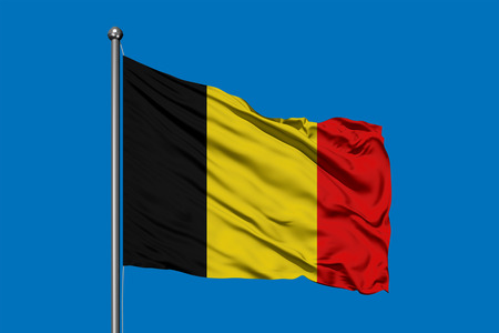Flag of Belgium waving in the wind against deep blue sky. Belgian flag.
