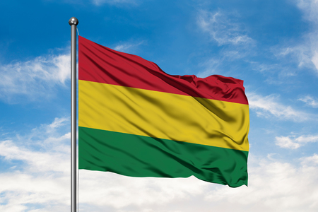 Flag of Bolivia waving in the wind against white cloudy blue sky. Bolivian flag.