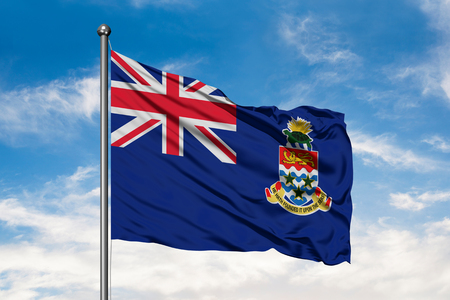 Flag of Cayman Islands waving in the wind against white cloudy blue sky.
