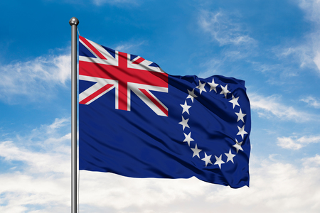 Flag of Cook Islands waving in the wind against white cloudy blue sky. Stock Photo
