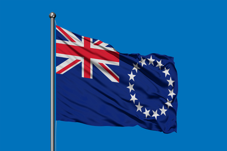 Flag of Cook Islands waving in the wind against deep blue sky.