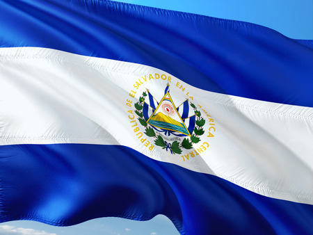 Flag of El Salvador waving in the wind against deep blue sky. High quality fabric.