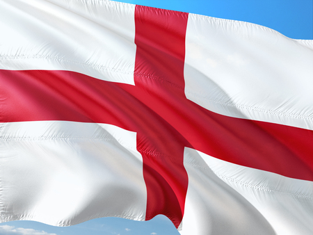 Flag of England waving in the wind against deep blue sky. High quality fabric. Stock Photo