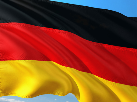 Flag of Germany waving in the wind against deep blue sky. High quality fabric.