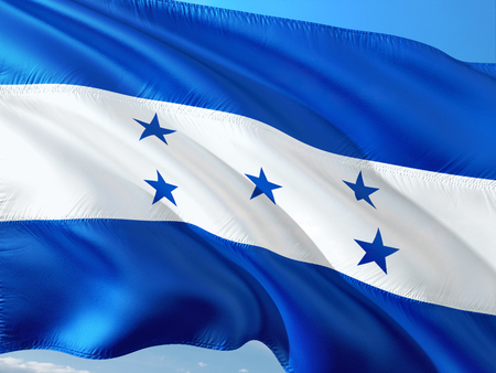 Flag of Honduras waving in the wind against deep blue sky. High quality fabric.