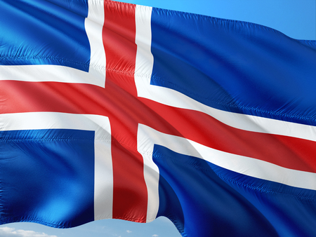 Flag of Iceland waving in the wind against deep blue sky. High quality fabric. Stock Photo