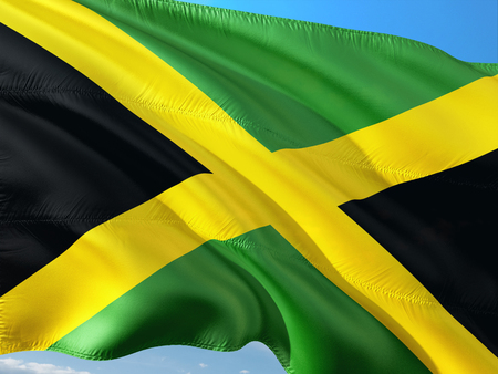 Flag of Jamaica waving in the wind against deep blue sky. High quality fabric. 免版税图像 - 114290071
