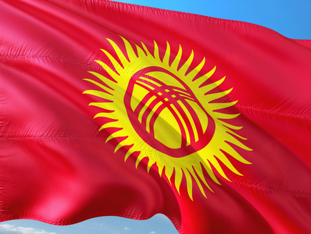 Flag of Kyrgyzstan waving in the wind against deep blue sky. High quality fabric.