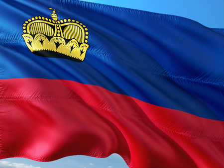 Flag of Liechtenstein waving in the wind against deep blue sky. High quality fabric.