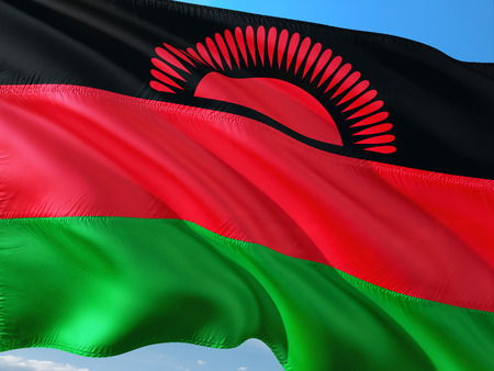 Flag of Malawi waving in the wind against deep blue sky. High quality fabric.