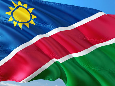 Flag of Namibia waving in the wind against deep blue sky. High quality fabric.