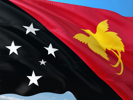 Flag of Papua New Guinea waving in the wind against deep blue sky. High quality fabric. Stock Photo