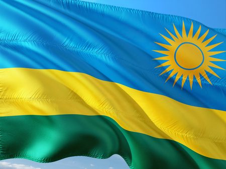 Flag of Rwanda waving in the wind against deep blue sky. High quality fabric.