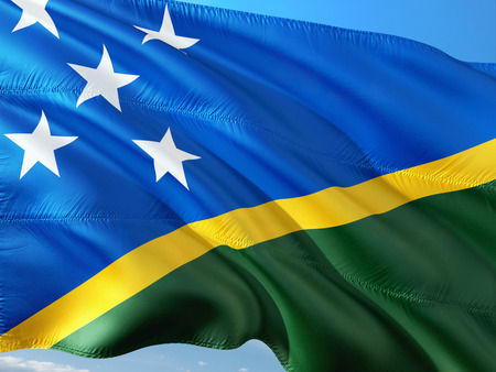 Flag of Solomon Islands waving in the wind against deep blue sky. High quality fabric.