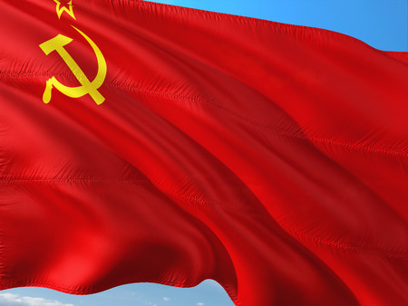 Flag of Soviet Union waving in the wind against deep blue sky. High quality fabric. Stock Photo