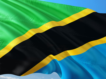 Flag of Tanzania waving in the wind against deep blue sky. High quality fabric. 스톡 콘텐츠