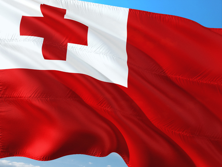 Flag of Tonga waving in the wind against deep blue sky. High quality fabric.