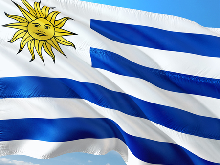 Flag of Uruguay waving in the wind against deep blue sky. High quality fabric. 写真素材