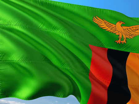 Flag of Zambia waving in the wind against deep blue sky. High quality fabric.