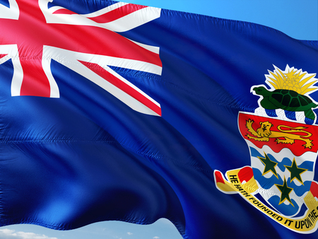 Flag of Cayman Islands waving in the wind against deep blue sky. High quality fabric. Stock Photo