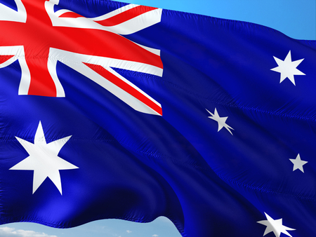 Flag of Australia waving in the wind against deep blue sky. High quality fabric.