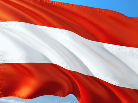 Flag of Austria waving in the wind against deep blue sky. High quality fabric.