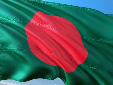 Flag of Bangladesh waving in the wind against deep blue sky. High quality fabric.