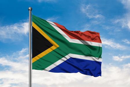 Bandiera del Sud Africa che fluttua nel vento contro il cielo blu nuvoloso bianco. Bandiera sudafricana. Archivio Fotografico