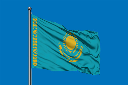 Flag of Kazakhstan waving in the wind against deep blue sky. Kazakh flag.