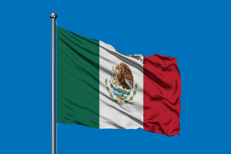 Flag of Mexico in the wind against deep blue sky. Mexican flag.