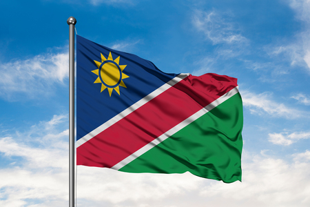 Flag of Namibia waving in the wind against white cloudy blue sky. Namibian flag. 免版税图像