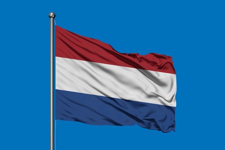 Flag of Netherlands waving in the wind against deep blue sky. Dutch flag. Stock Photo