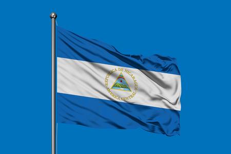 Flag of Nicaragua waving in the wind against deep blue sky. Nicaraguan flag.