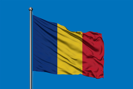 Flag of Romania waving in the wind against deep blue sky. Romanian flag.