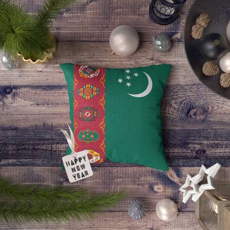 Happy New Year tag with Turkmenistan flag on pillow. Christmas decoration concept on wooden table with lovely objects. Stock Photo