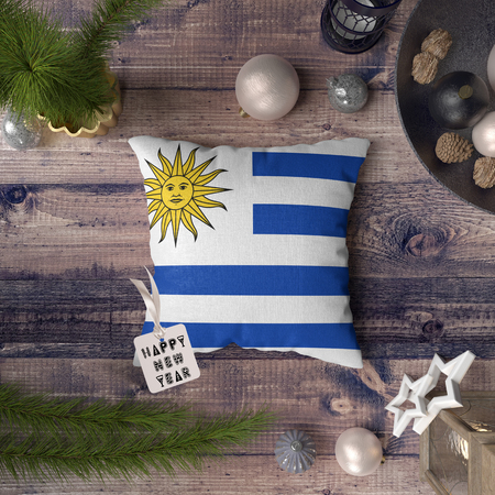 Happy New Year tag with Uruguay flag on pillow. Christmas decoration concept on wooden table with lovely objects.