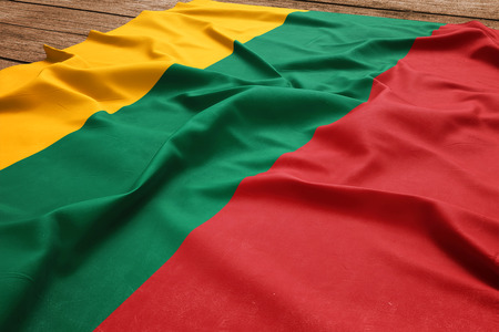 Flag of Lithuania on a wooden desk background. Silk Lithuanian flag top view. Фото со стока