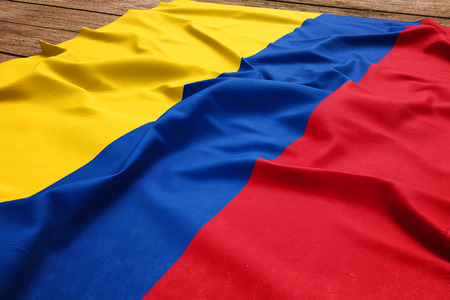 Flag of Colombia on a wooden desk background. Silk Colombian flag top view.