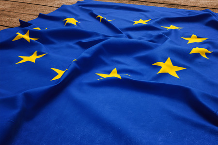 Flag of European Union on a wooden desk background. Silk EU flag top view.