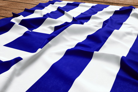 Flag of Greece on a wooden desk background. Silk Greek flag top view.
