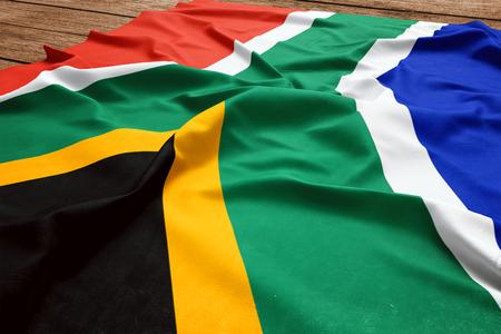 Bandiera del Sudafrica su uno sfondo di scrivania in legno. Vista dall'alto di seta bandiera sudafricana. Archivio Fotografico