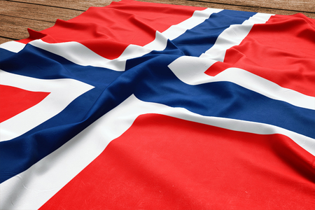 Flag of Svalbard And Jan Mayen on a wooden desk background. Silk flag top view.
