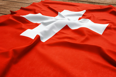 Flag of Switzerland on a wooden desk background. Silk Swiss flag top view.