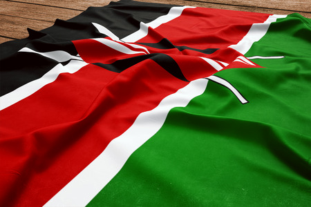 Flag of Kenya on a wooden desk background. Silk flag top view. Stock Photo