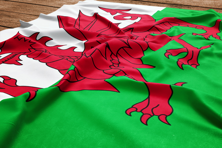 Flag of Wales on a wooden desk background. Silk Welsh flag top view. 版權商用圖片