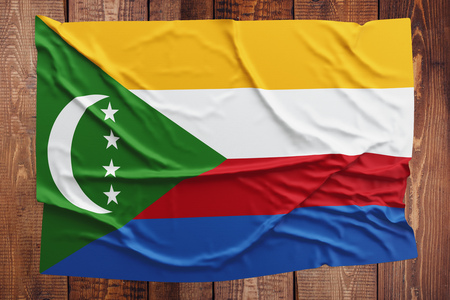 Flag of Comoros on a wooden table background. Wrinkled Comoran flag top view. Stock Photo