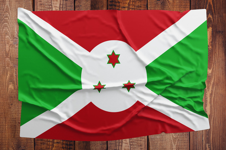 Flag of Burundi on a wooden table background. Wrinkled Burundian flag top view. Stock Photo