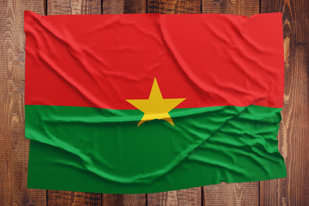 Flag of Burkina Faso on a wooden table background. Wrinkled Burkinabe flag top view. Stock Photo