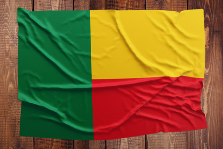 Flag of Benin on a wooden table background. Wrinkled Beninese flag top view. Stock Photo